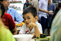 Curious Vietnamese boy (local) observes the westerners while eating his pho